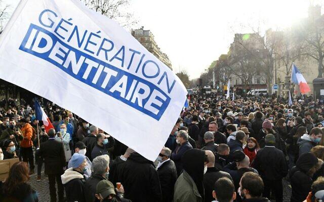 Des membres et partisans du groupe d'extrême droite Génération identitaire et un drapeau du mouvement lors d'une manifestation contre sa possible dissolution, à Paris, le 20 février 2021. (Crédit : Bertrand GUAY / AFP)