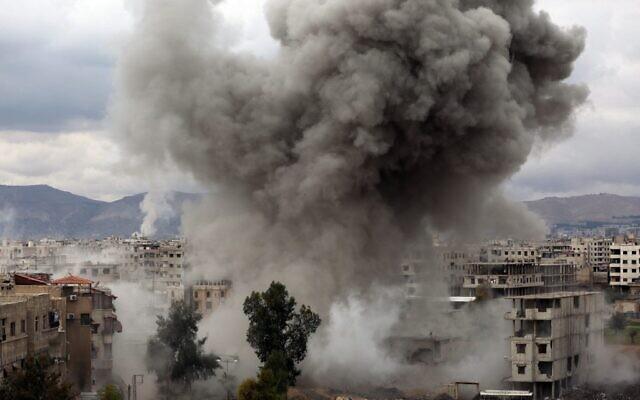 Des bombardements du gouvernement syrien sur Kafr Batna, dans la région assiégée de la Ghouta orientale à la périphérie de la capitale Damas, en Syrie, le 22 février 2018. (Crédit : AMER ALMOHIBANY / AFP)