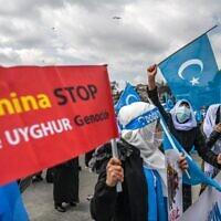 Des membres de la minorité musulmane ouïgoure brandissent des pancartes et des drapeaux du Turkestan oriental alors qu'elles manifestent pour demander des nouvelles de leurs proches et pour exprimer leur inquiétude quant à la ratification d'un traité d'extradition entre la Chine et la Turquie, près du consulat de Chine à Istanbul, le 8 mars 2021, lors de la Journée internationale de la femme. (Crédit : Ozan KOSE / AFP)
