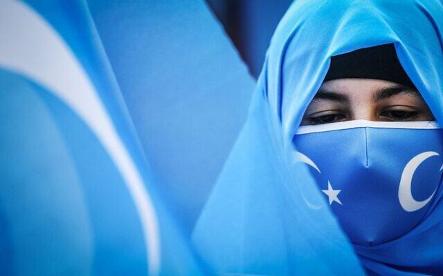 Des membres de la minorité musulmane ouïghoure tiennent des pancartes et des drapeaux du Turkestan oriental alors qu'elles manifestent pour avoir des nouvelles de leurs proches et exprimer leur inquiétude quant à la ratification d'un traité d'extradition entre la Chine et la Turquie, près du consulat de Chine à Istanbul, le 8 mars 2021, lors de la Journée internationale de la femme.  (Crédit : Ozan KOSE / AFP)