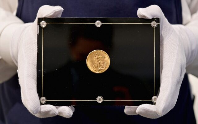 Un employé de Sotheby's porte une pièce de monnaie Double Eagle de 1933 à l'occasion de la vente aux enchères «Trois trésors - Collectés par Stuart Weitzman», dédiée aux trois trésors de la collection personnelle du créateur de mode et collectionneur, chez Sotheby's, le 11 mars 2021, à New York. (Crédit : Angela Weiss / AFP)