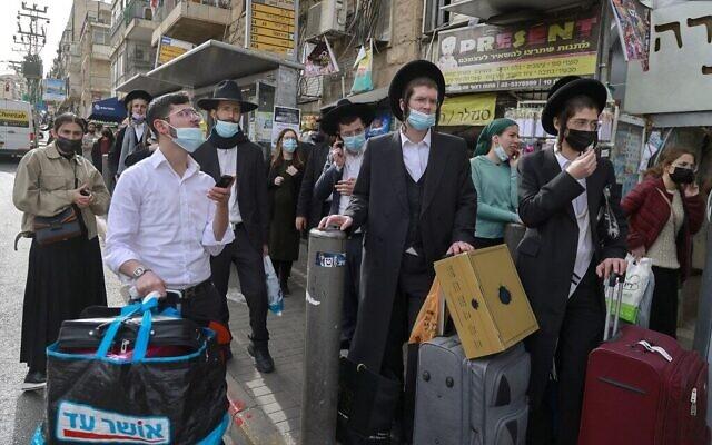 Des Israéliens attendent à un arrêt de bus du quartier ultra-orthodoxe de Méa Shéarim, à Jérusalem, le 11 mars 2021. (Crédit : MENAHEM KAHANA / AFP)