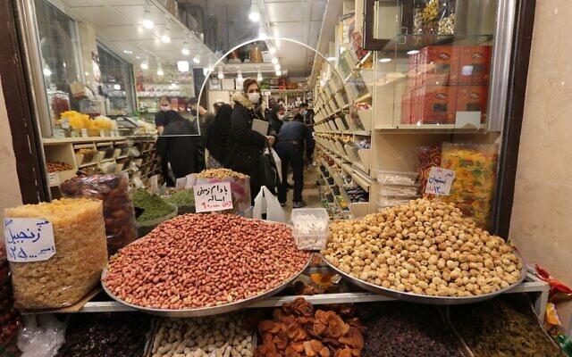 Des Iraniens masqués font des achats en pleine pandémie de Covid-19, au Bazar Tajrish à Téhéran, le 17 mars 2021, alors que l'Iran se prépare à célébrer Nowruz, le nouvel an iranien. (Crédit ATTA KENARE / AFP)