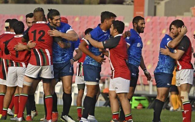 Des joueurs de rugby israéliens (en bleu) et émiratis se saluent après leur premier match amical à Dubaï, le 19 mars 2021. (Karim SAHIB/AFP)