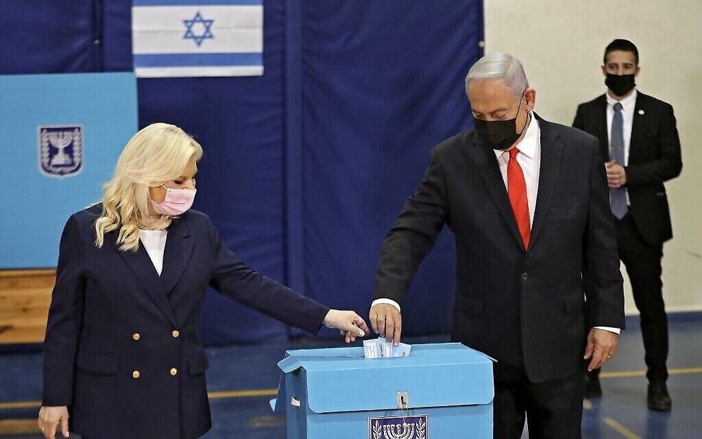 Le Premier ministre Benjamin Netanyahu et son épouse Sara votent à Jérusalem le 23 mars 2021. (Crédit : RONEN ZVULUN / POOL / AFP)
