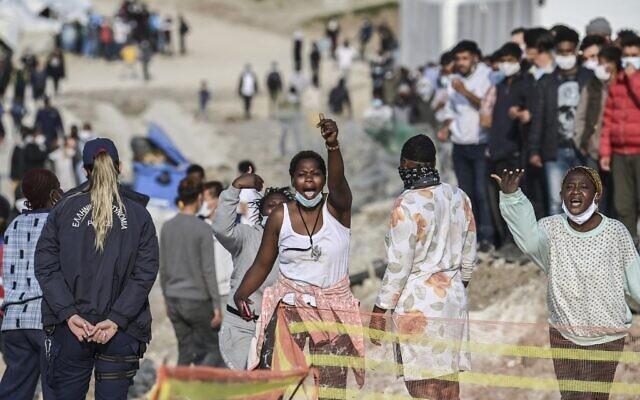 Des femmes migrantes africaines crient « liberté » à l'intérieur du nouveau camp de réfugiés de Kara Tepe à Mytilène, à Lesbos, le 29 mars 2021. (Crédit : ARIS MESSINIS / AFP)