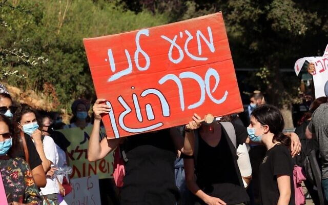 """Un manifestant brandit une pancarte indiquant """"nous méritons un salaire décent"""" devant le ministère des Finances à Jérusalem lors d'une manifestation pour les travailleurs sociaux, le 14 juillet 2020 à Jérusalem, en Israël. (Autorisation du Syndicat des travailleurs sociaux d'Israël)"""
