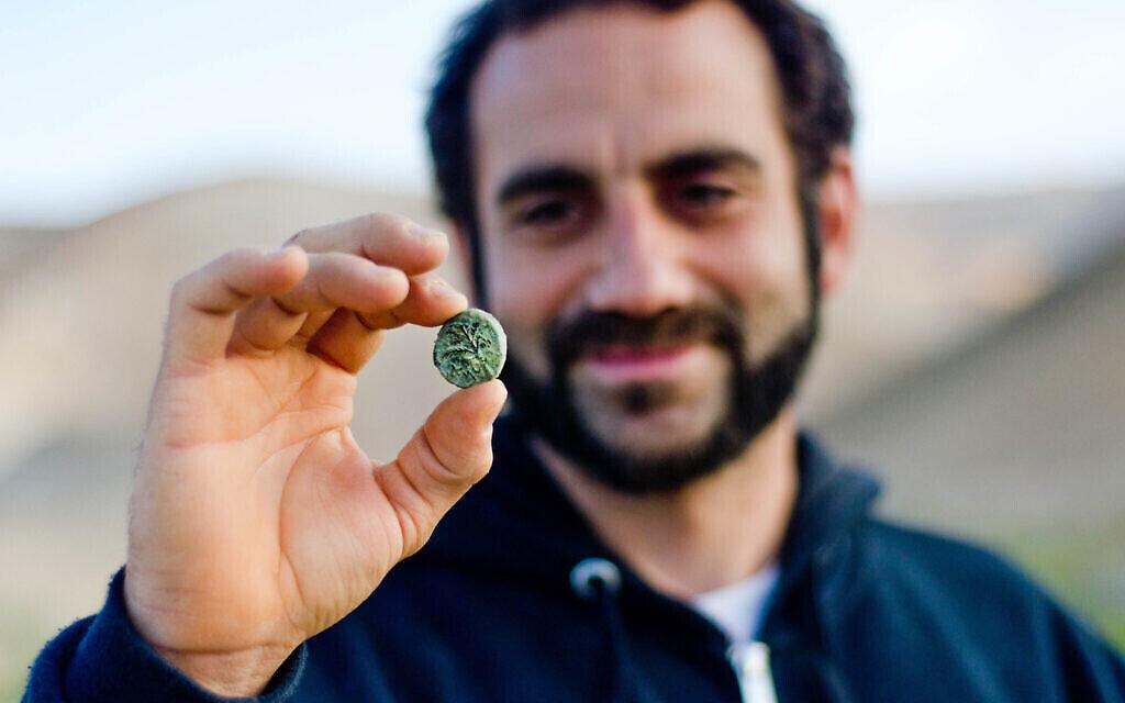 L'archéologue Hagay Hamer tient une pièce de Bar Kokhba découverte dans le désert. (Crédit : Yoli Schwartz, Autorité israélienne des antiquités)