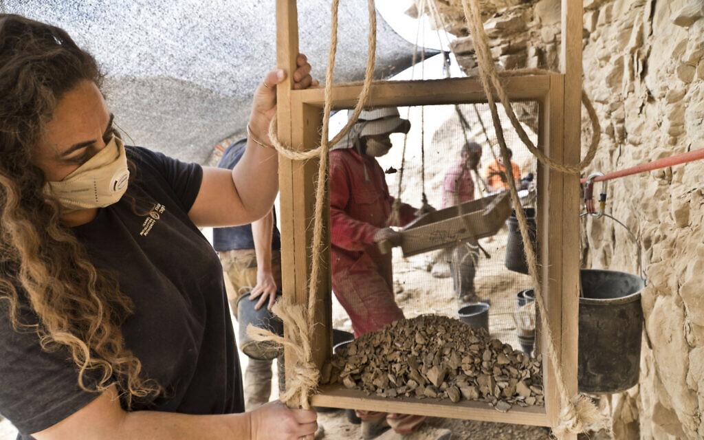 Le travail de tamisage à l'entrée de la grotte de Murabaat. (Crédit : Yoli Schwartz, Autorité israélienne des antiquités)