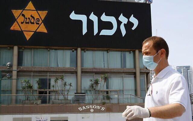 Illustration : un homme portant un masque et un équipement de protection se tient près d'une bannière représentant une étoile jaune de l'époque nazie, à Tel Aviv, le 21 avril 2020. (Jack Guez / AFP via Getty Images)