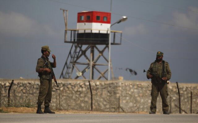 Des gardes palestiniens du Hamas se tiennent près d'une tour de guet égyptienne à la frontière avec l'Égypte à Rafah, dans le sud de la bande de Gaza. (Crédit : AP/Hatem Moussa)