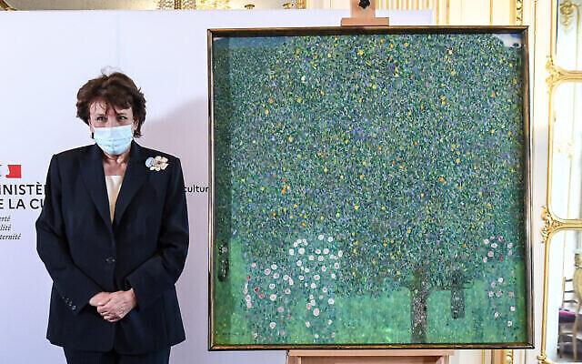 """La ministre française de la Culture, Roselyne Bachelot, pose à côté d'une peinture à l'huile de Gustav Klimt peinte en 1905 intitulée """"Rosiers sous les arbres"""", lors d'une cérémonie au musée d'Orsay à Paris, le 15 mars 2021. (Crédit : Alain Jocard / Pool Photo via AP)"""