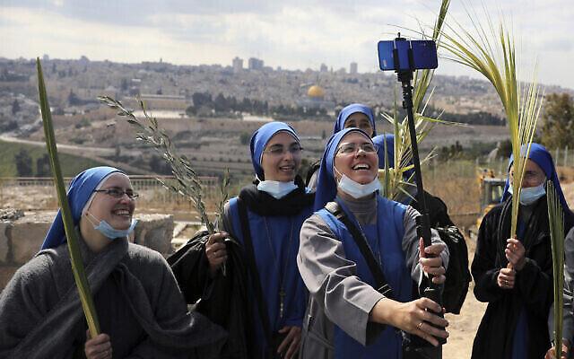 Des religieuses posent pour un selfie sur le mont des Oliviers pendant le dimanche des rameaux à Jérusalem, le 28 mars 2021. (Crédit : AP Photo/ Mahmoud Illean)