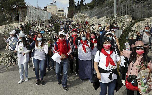 Des fidèles chrétiens lors d'une procession de rameaux sur le mont des Oliviers, à Jérusalem, le 28 mars 2021. (Crédit : AP Photo/Mahmoud Illean)