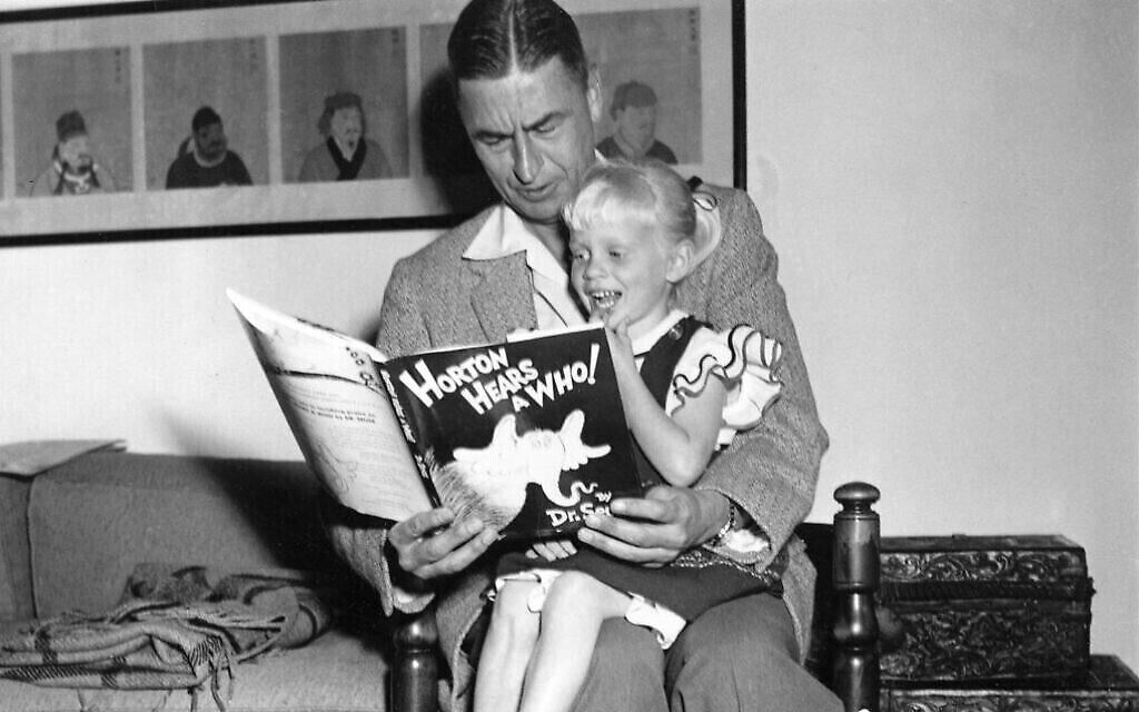 """L'auteur et illustrateur Theodor Seuss Geisel, connu sous le nom de DrSeuss, lit un passage de son livre """"Horton Hears a Who !"""" à Lucinda Bell, âgée de quatre ans, dans sa maison de La Jolla, en Californie, le 20 juin 1956. (Photo AP)"""