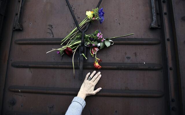 Une femme place des fleurs sur un wagon de train à la vieille gare de Thessalonique, en Grèce, à l'occasion du 74e anniversaire de la rafle et de la déportation de ses Juifs vers les camps d'extermination nazis pendant la Seconde Guerre mondiale, le 19 mars 2017. (Crédit : Giannis Papanikos/AP)