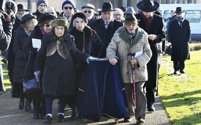 Un groupe de survivants de la Shoah transporte un cercueil couvert contenant les restes de six victimes non identifiées de la Shoah pour les enterrer au Nouveau Cimetière de la United Synagogue à Bushey, en Angleterre, le 20 janvier 2019. (John Stillwell/PA via AP)