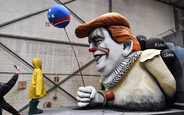 Un homme prend une photo d'un char de carnaval satirique représentant le président américain Donald Trump sous les traits du clown du film d'horreur Pennywise lors d'une avant-première dans un hall à Cologne, en Allemagne, le 18 février 2020. (AP Photo/Martin Meissner)