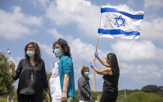 Des personnels médicaux et des malades, portant des masques, brandissent des drapeaux israéliens alors que les forces aériennes font une démonstration de vol acrobatique au dessus de l'hôpital Hillel Yaffe à Hadera, dans le nord d'Israël, le 29 avril 2020. (Crédit ;Ariel Schalit/AP)