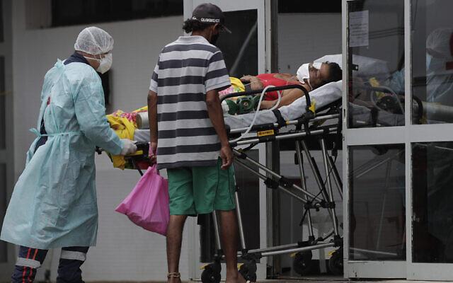 Des soignants reçoivent un patient soupçonné d'avoir le COVID-19 à l'hôpital public HRAN de Brasilia, au Brésil, le 8 mars 2021. (Crédit : Eraldo Peres/AP)