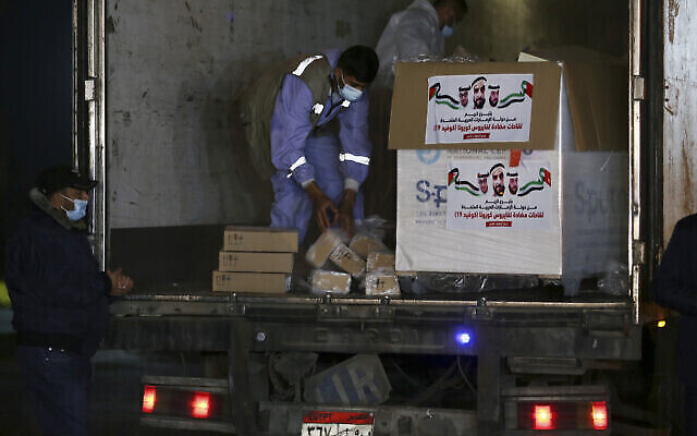 Les agents de police du Hamas montent la garde lors du déchargement d'un camion transportant 40 000 doses de vaccin russe anti-COVID-19 Sputnik V à son arrivée dans la bande de Gaza, au poste-frontière de Rafah avec l'Égypte, le 11 mars 2021. (Crédit : Adel Hana/AP)