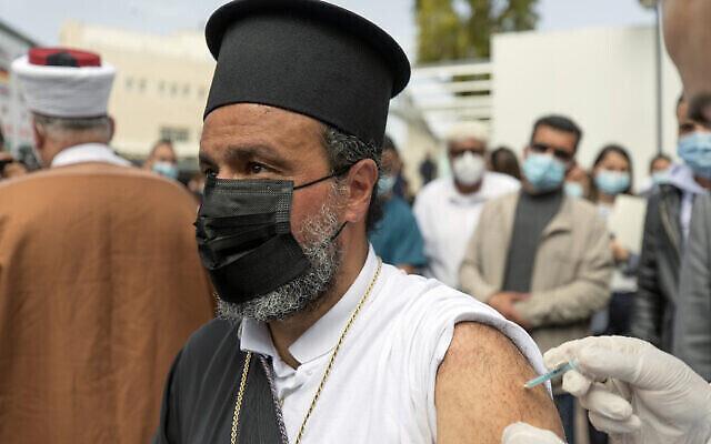 Photo d'illustration :  Un prêtre chrétien palestinien se fait vacciner contre la COVID-19 pendant une campagne de vaccination des travailleurs essentiels au ministère de la Santé de Ramallah, en Cisjordanie, le 21 mars 2021. (Crédit :  Nasser Nasser/AP)