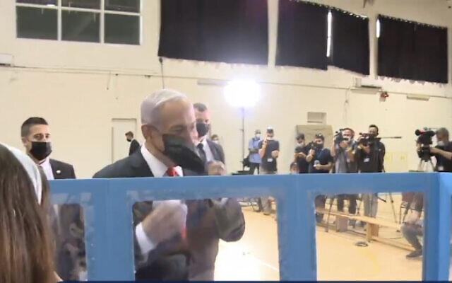 Le Premier ministre Benjamin Netanyahu baisse son masque pour confirmer son identité lors du vote à Jérusalem le 23 mars 2021. (Capture d'écran)