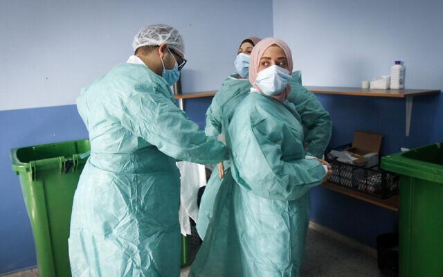 Des personnels soignants d'un hôpital de la ville de Naplouse, en Cisjordanie, dont les employés ont été vaccinés contre la COVID-19 dans la matinée après la livraison de doses de vaccin depuis Israël, le 3 février 2021. (Crédit : Nasser Ishtayeh/Flash90)