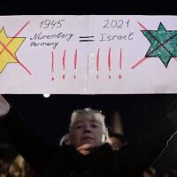 Une manifestante compare apparemment le certificat de vaccination vert d'Israël aux lois nazies obligeant les Juifs à porter l'étoile jaune à Tel Aviv, le 15 février 2021. (Tomer Neuberg/FLASH90)