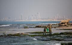 Des soldats nettoient le goudron sur la plage de Palmachim suite à une marée noire en mer, qui a recouvert la majeure partie des côtes israéliennes, le 22 février 2021. (Yonatan Sindel/Flash90)