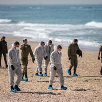 Des soldats israéliens aident à nettoyer du goudron sur la plage Palmachim suite à une fuite de pétrole qui a touché la plus grande partie de la côte israélienne, le 22 février 2021. (Crédit :  Yonatan Sindel/Flash90)