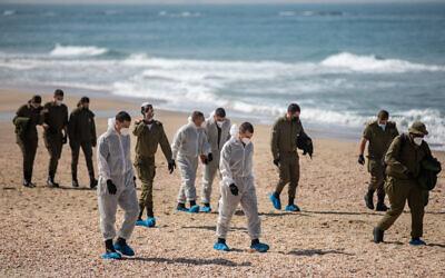 Des soldats israéliens aident à nettoyer du goudron sur la plage Palmachim suite à une fuite de pétrole qui a touché une large partie de la côte israélienne, le 22 février 2021. (Crédit : Yonatan Sindel/Flash90)