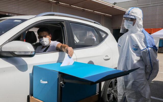 Un homme vote pendant une simulation d'un bureau de vote en voiture, en prévision des prochaines élections, à l'entrepôt de la commission centrale des élections à Modiin, le 23 février 2021. (Flash90)