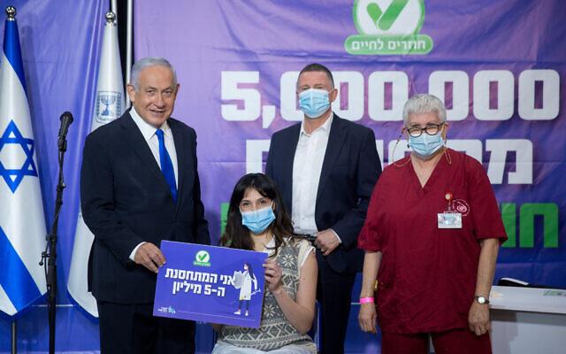 Le Premier ministre Benjamin Netanyahu, à gauche, et le ministre de la Santé Yuli Edelstein, à droite, dans un centre de vaccination de la Leumit contre le coronavirus à Tel Aviv avec la cinq-millionième Israélienne à avoir reçu une dose de vaccin (hors cadre), le 8 mars 2021. (Crédit : Miriam Alster/Flash90)