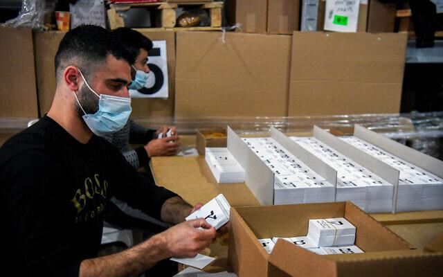 Des employés palestiniens de l'imprimerie Palphot dans l'implantation de Karnei Shomron, au nord de la Cisjordanie, organisent des bulletins de vote en vue des prochaines élections en Israël, le 9 mars 2021. (Flash90)