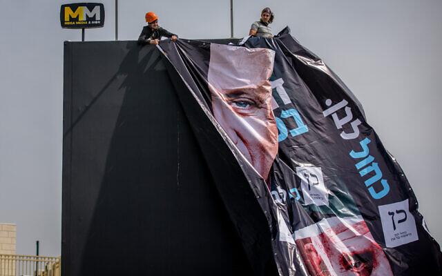 Des ouvriers accrochent une affiche électorale pour le parti Kakhol lavan de Benny Gantz, montrant Gantz et le Premier ministre Benjamin Netanyahu à Jérusalem, le 11 mars 2012. (Crédit :  Yonatan Sindel/Flash90)