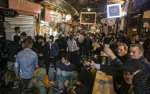 Des Israéliens dans des bars du marché Mahane Yehuda de Jérusalem, le 12 mars 2021. (Olivier Fitoussi/Flash90)