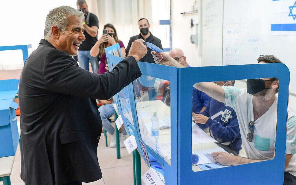 Le chef du parti Yesh Atid, Yair Lapid, et son épouse Lihi déposent leur bulletin de vote dans un bureau de vote à Tel Aviv, lors des élections pour la Knesset, le 23 mars 2021. (Tomer Neuberg/Flash90)