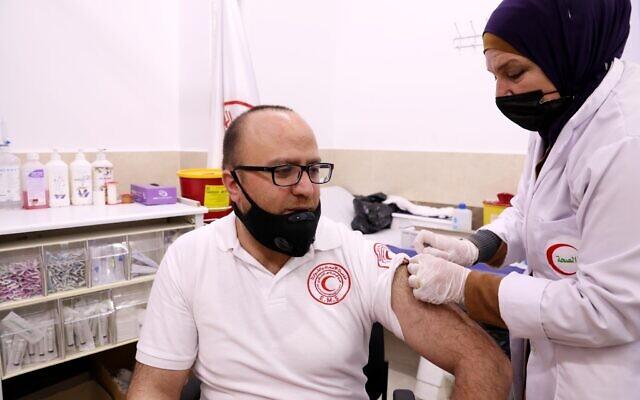 Des Palestiniens se font vacciner contre la  COVID-19 dans la ville de Hébron, en Cisjordanie, le 25 mars 2021. (Crédit :  Wisam Hashlamoun/Flash90)