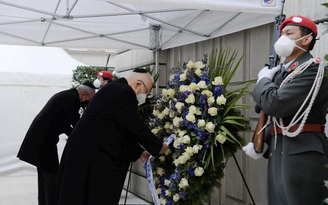 Le président israélien Reuven Rivlin (au centre) et le président autrichien Alexander Van der Bellen participent à une cérémonie devant un monument aux victimes de la Shoah à Vienne, le 17 mars 2021. (Amos Ben Gershom/GPO)