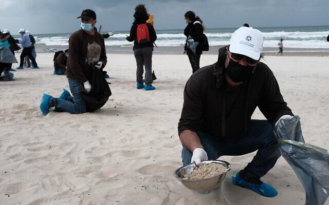 Les Israéliens nettoient la plage de Bat Yam  suite à une marée noire qui a pollué la plus grande partie de la ligne côtière, le 2 mars 2021. (Crédit : Tomer Neuberg/Flash90)