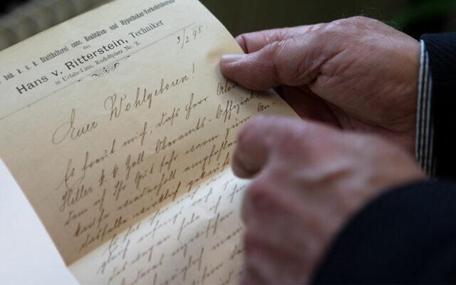 L'historien autrichien Roman Sandgruber tient une lettre écrite par Alois Hitler adressée au fonctionnaire chargé de l'entretien des routes Josef Radlegger, à Linz, en Autriche, le 3 mars 2021. (Crédit ; ALEX HALADA / AFP)