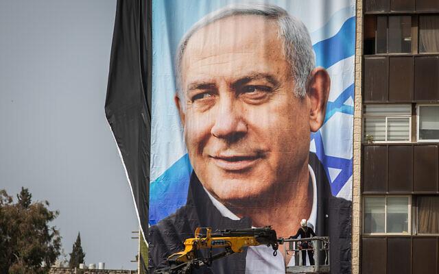 Des employés israéliens accrochent de grandes affiches de la campagne électorale du parti Likud, dans le cadre de la campagne électorale du Likud, à Jérusalem, le 10 mars 2021. (Yonatan Sindel/Flash90)