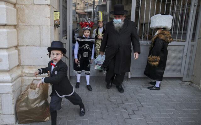 Des enfants juifs ultra-orthodoxes sont déguisés pour célébrer Pourim dans le quartier de Mea Shearim à Jérusalem, le 25 février 2021. (AHMAD GHARABLI / AFP)