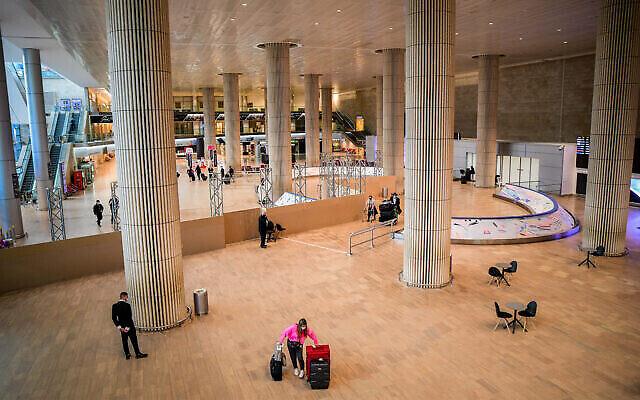 Des passagers marchent dans le hall des arrivées de l'aéroport international Ben Gurion, près de Tel Aviv, le 8 mars 2021. (Avshalom Sassoni / Flash90)