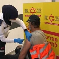 Un ouvrier palestinien se fait vacciner par le personnel du Magen David Adom israélien au point de contrôle de Shaar Efraim en Cisjordanie, le 4 mars 2021. (COGAT)