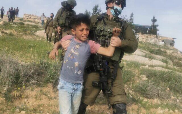 Un soldat israélien avec un enfant palestinien à al-Rakiz, dans les collines du sud d'Hébron, le mercredi 10 mars 2021 (Crédit : Nasr Nawajaa/B'Tselem).