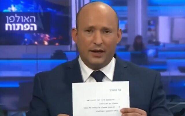 Naftali Bennett montre une promesse signée de ne jamais servir dans un gouvernement dirigé par Yair Lapid, le 21 mars 2021. (Crédit : capture d'écran/Vingtième chaîne)