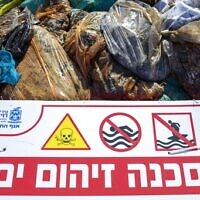 """Un panneau qui dit """"Danger, mer polluée"""" sur une plage de Haïfa, dans le nord d'Israël, près de sacs remplis de goudron collecté par les bénévoles suite à une marée noire en mer méditerranée, le 28 février 2021. (Crédit :  AP Photo/Ariel Schalit)"""