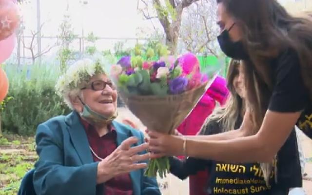 Un bénévole de l'Association d'aide immédiate aux survivants de la Shoah offre des fleurs à Frieda Kliger pour son 100e anniversaire, le 14 mars 2021. (Capture d'écran Douzième chaîne)